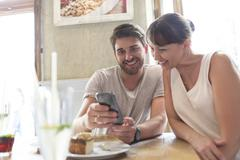 Couple texting with cell phone at cafe table Stock Photos