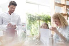 Waiter taking order from mother and daughter in cafe - stock photo