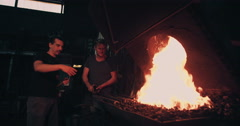 Blacksmith working iron on a forge with fire in Slow Motion - stock footage