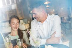 Father and daughter drinking lemonade at cafe table - stock photo