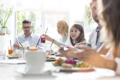 Family eating at cafe table - stock photo