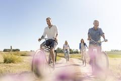 Stock Photo of Family riding bicycles on sunny rural dirt road
