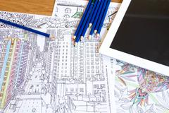Adult colouring books with  pencils, new stress relieving trend, mindfulness - stock photo