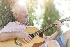 Senior man playing guitar against tree trunk Stock Photos