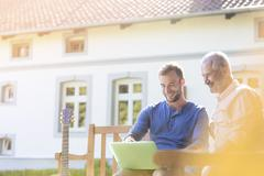 Stock Photo of Father and adult son using laptop on garden bench