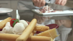Italian cooking: Cut the bacon,  foreground appetizer with salami and cheese Stock Footage