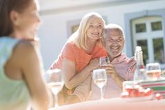 Senior couple smiling and drinking wine on sunny patio - stock photo