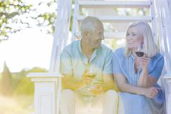 Senior couple drinking wine on summer stairs - stock photo