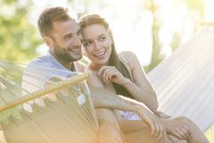 Affectionate young couple smiling in summer hammock Stock Photos