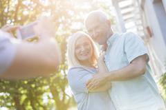 Man photographing senior couple outdoors - stock photo