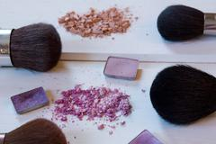 women's accessories cosmetics. Makeup brushes and crushed eyeshadow on wo - stock photo
