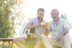Stock Photo of Father and adult son toasting beer mugs and playing guitar outdoors