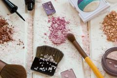 Women's accessories cosmetics. Makeup brushes and crushed eyeshadow on wo Stock Photos