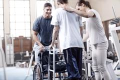 Physical therapists helping man with walker - stock photo
