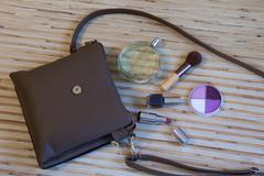 Open leather bag with women cosmetics - stock photo