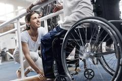 Physical therapist preparing man in wheelchair - stock photo