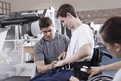 Physical therapists attaching equipment to man in wheelchair - stock photo