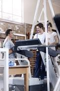 Physical therapists helping man on treadmill Stock Photos