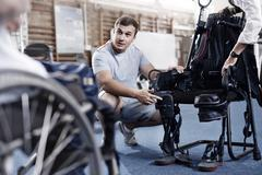 Physical therapist explaining equipment to man in wheelchair Stock Photos