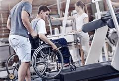 Physical therapists guiding man in wheelchair on treadmill - stock photo