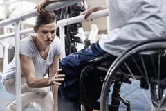 Physical therapist checking man's knee Stock Photos