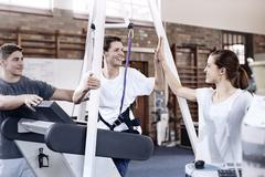 Smiling man high fiving physical therapist Stock Photos