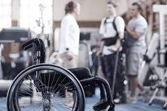 Man receiving physical therapy with wheelchair in foreground - stock photo