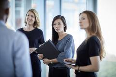 Attentive businesswomen listening to businessman - stock photo