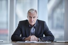 Portrait serious senior businessman in conference room - stock photo