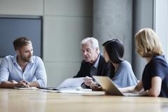 Business people discussing paperwork in conference room Stock Photos