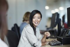 Smiling businesswoman talking to colleague in office Stock Photos