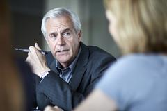 Senior businessman listening to businesswoman in meeting - stock photo