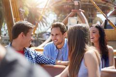 Smiling friends talking on amusement park ride Kuvituskuvat