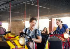 Laughing young men riding bumper cars at amusement park - stock photo