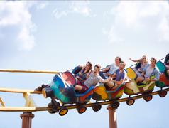 Friends cheering and riding roller coaster at amusement park Stock Photos