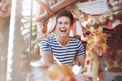 Enthusiastic young man riding carousel at amusement park Stock Photos