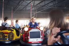 Young man riding bumper cars at amusement park - stock photo