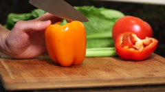 Man cleans out orange bell pepper seeds close up Stock Footage