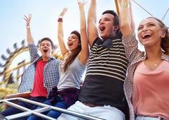 Cheering friends riding amusement park ride Stock Photos