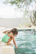 Toddler girl testing the water at edge of swimming pool - stock photo