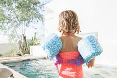 Toddler girl in water wings at edge of swimming pool - stock photo