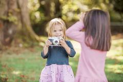 Toddler girls playing with camera in park - stock photo