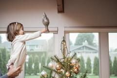 Toddler girl putting star on Christmas tree - stock photo