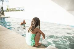 Toddler girl at edge of swimming pool Stock Photos