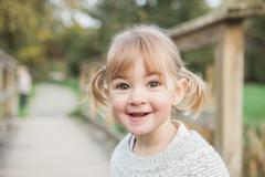 Stock Photo of Portrait smiling toddler girl with pigtails