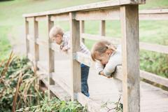 Toddler children leaning on footbridge railing in park Stock Photos