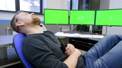 security guard sleeps in front of a green screens, he suddenly wakes up and - stock footage