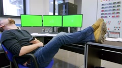 a security guard sleeps in front of a green screens, he suddenly wakes up and - stock footage
