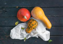 Three pumpkins od different shapes and color with a piece of white linen fabr - stock photo