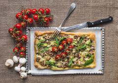 Rustic square mushroom pizza with fresh arugula and cherry-tomatoes on a silv Stock Photos